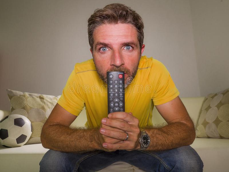 Stressed man watching football game on TV sitting at home living room couch excited and with expression of crazy intense emotion. 30s to 40s attractive and stock image