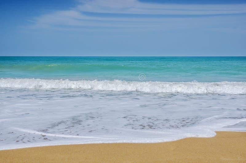 S?tta p? land sand och sl?sa havet i bl? himmel arkivfoto
