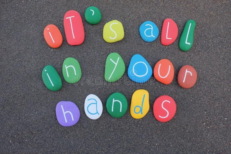 ` s tutta nella vostra frase concettuale delle mani, di vita e di affari composta con le pietre multicolori sopra la sabbia nera illustrazione di stock