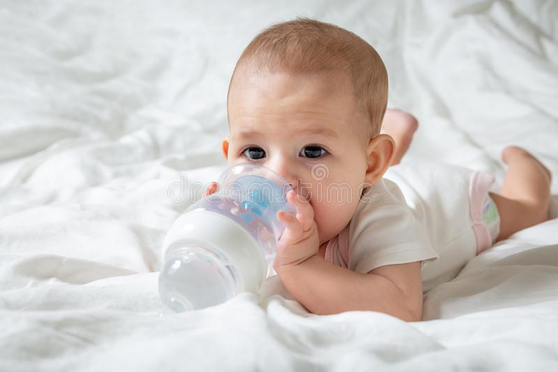 S?uglingsbaby mit den gro?en braunen Augen, die auf dem wei?en Bett mit spezieller Flasche Wasser mit Nippel liegen Versucht, sie lizenzfreies stockbild