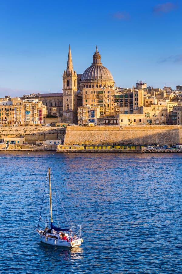 ` S Vallettas, Malta - StPaul-Kathedrale in der goldenen Stunde an Malta-` s Hauptstadt Valletta mit Segelboot lizenzfreie stockfotos