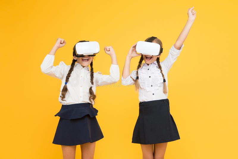 S? verkligt Lyckliga ungar använder modern teknologi Virtuell verklighet små flickor i VR-hörlurar med mikrofon Framtida utbildni arkivbilder