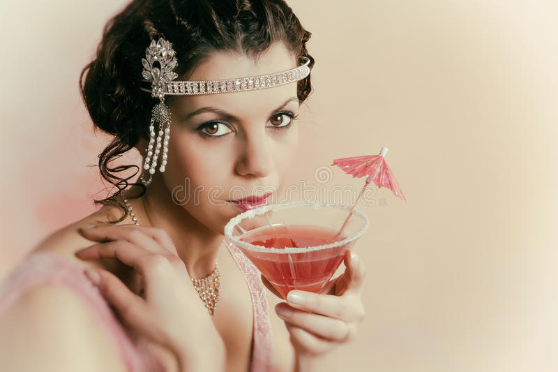 1920s vintage lady drinking. Beautiful young vintage 1920s woman with headband and flapper dress drinking a cocktail royalty free stock photography