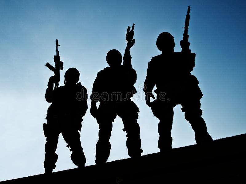 S.W.A.T. team. Silhouettes of S.W.A.T. officers holding their guns stock images