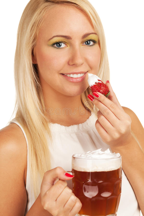That's why I like beer for. Seductive girl uses beer scum as whipped cream for strawberry stock photography