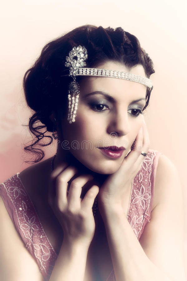 1920s woman closeup. Closeup in vintage colors of a 1920s style young woman with diamond headdress and flapper dress royalty free stock photos