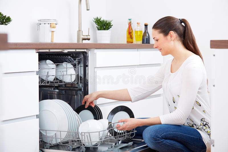 Download 20s Woman In Kitchen Empty Out The Dishwasher Stock Photo