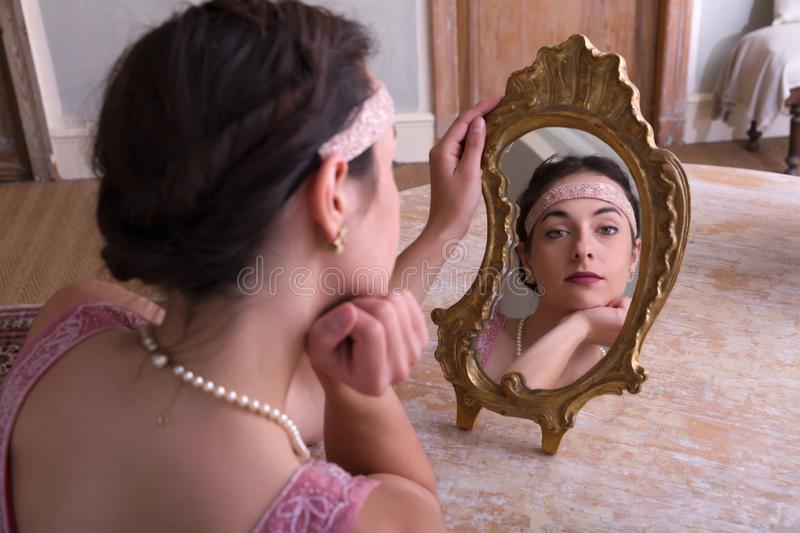 1920s woman looking in mirror. Sensual young woman in 1920s flapper dress and headband looking in an antique mirror royalty free stock photo