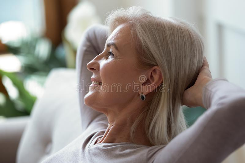 60s woman put hands behind head resting indoors enjoy weekend. Older 60s woman put hands behind head resting seated indoors enjoy summer day looking out window royalty free stock images