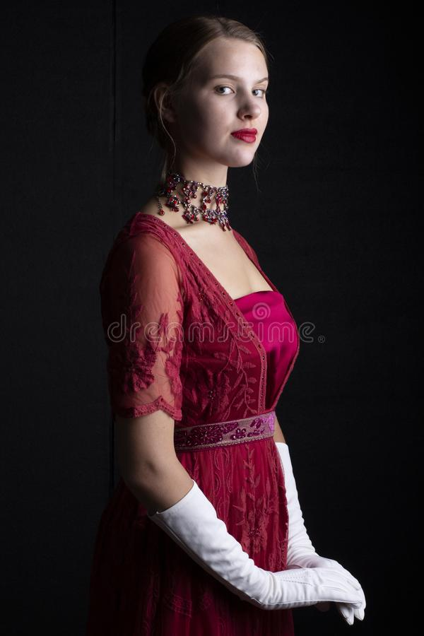 1910`s woman in red lace gown and crystal necklace. Early 20th century woman in red lace gown and crystal necklace on a black background stock image