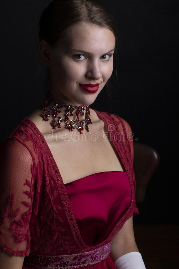 1910`s woman in red lace gown and crystal necklace. Early 20th century woman in red lace gown and crystal necklace on a black background stock photography