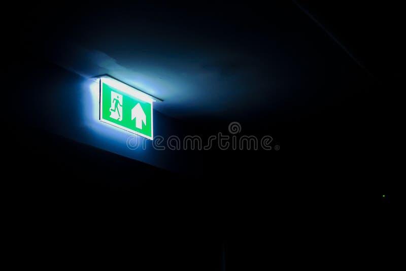 A saída de emergência assina dentro uma sala escura, com espaço da cópia imagem de stock