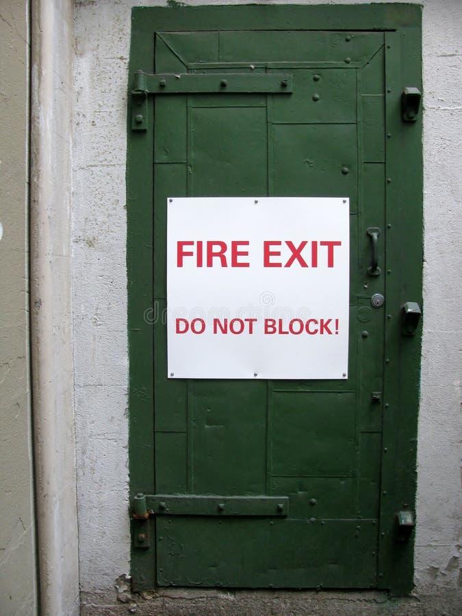 A saída de emergência não obstrui! sinal em uma porta verde fotos de stock