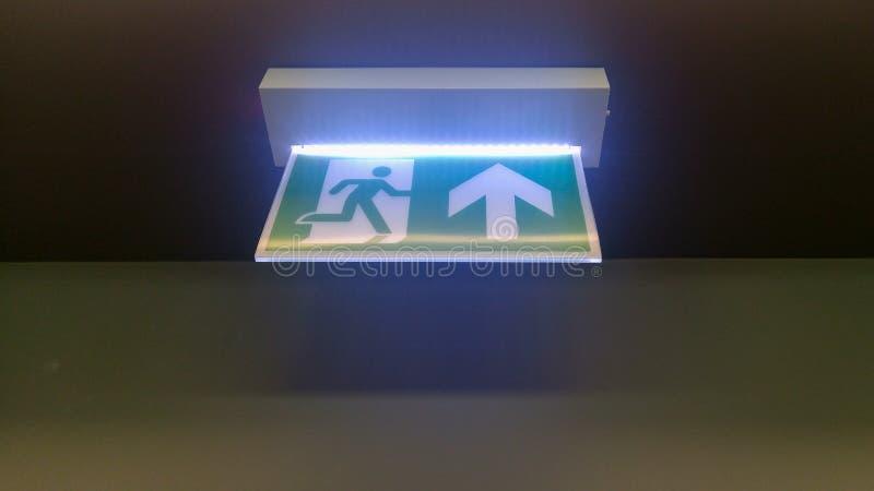 A saída de emergência verde pequena assina no escritório imagens de stock royalty free