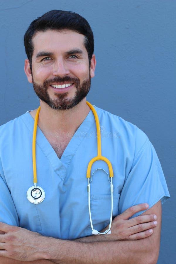 A saúde é a prioridade a mais grande Retrato do estúdio de um doutor masculino novo que sorri com confiança isolado no azul imagens de stock royalty free