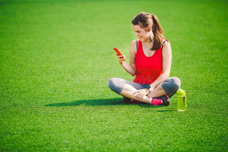 Saúde do esporte do tema assento bonito da moça que descansa na grama verde estádio do gramado usando technodogies No handphone n imagem de stock