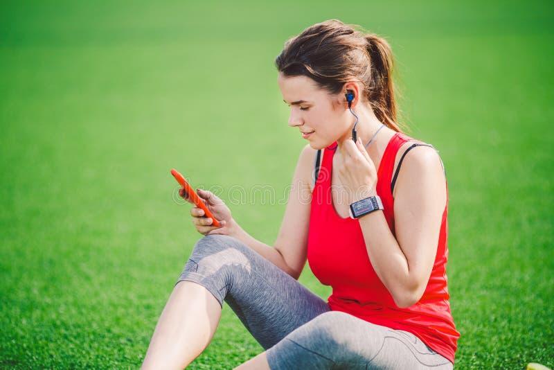 Saúde do esporte do tema assento bonito da moça que descansa na grama verde estádio do gramado usando technodogies No handphone n foto de stock royalty free