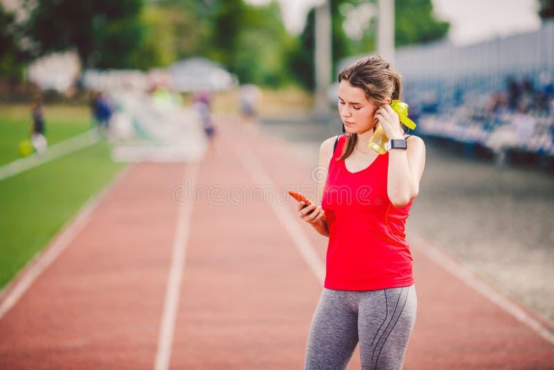 Saúde do esporte do tema posição da menina que descansa na trilha a estrada do estádio usa technodogies os fones de ouvido da ore fotografia de stock