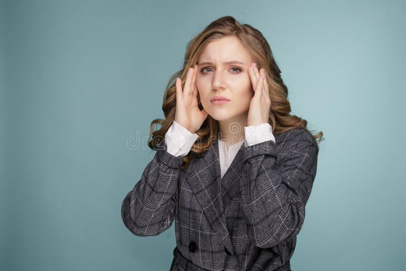 Saúde e dor Jovem mulher esgotada forçada que tem a dor de cabeça de tensão forte Retrato do close up da menina doente bonita foto de stock