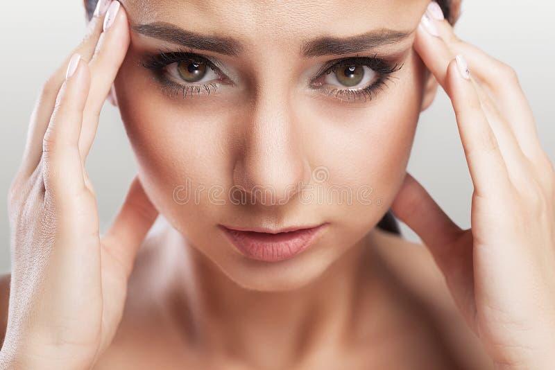 Saúde e dor Jovem mulher esgotada forçada que tem a dor de cabeça de tensão forte Retrato do close up de uma menina doente bonita foto de stock royalty free