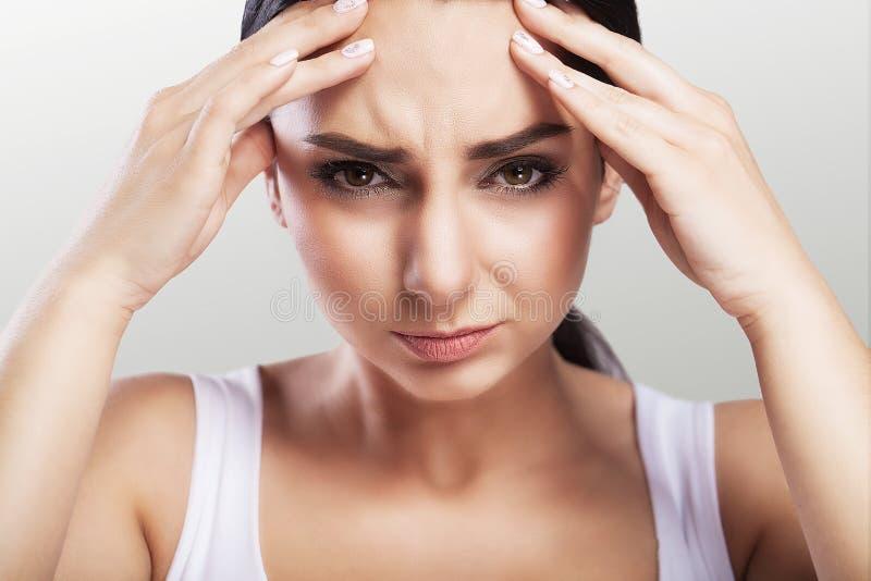Saúde e dor Uma jovem mulher cansado, esgotada que sofra de uma dor de cabeça severa da tensão Retrato de uma menina doente bonit foto de stock royalty free