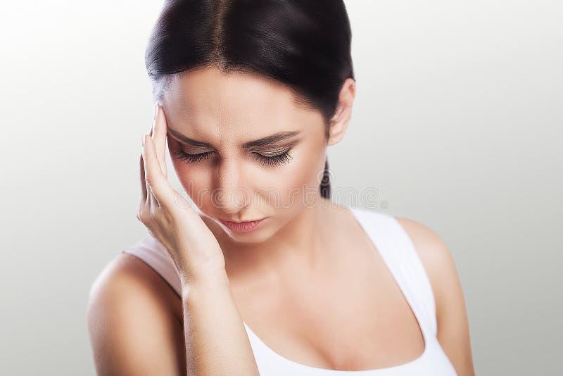 Saúde e dor Uma jovem mulher cansado, esgotada que sofra de uma dor de cabeça severa da tensão Retrato de uma menina doente bonit imagem de stock