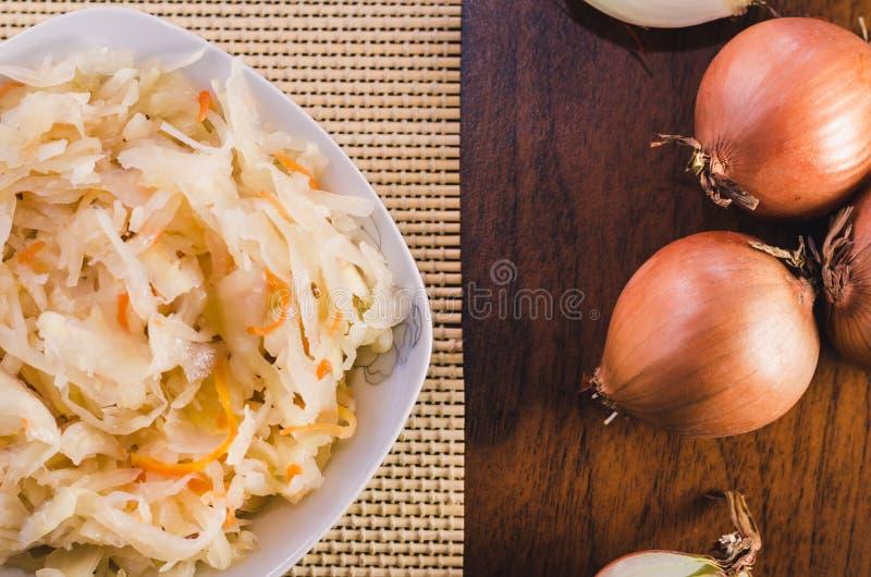 Sałatka sauerkraut i marchewki w białym talerzu i kilka cebulkowych żarówkach na drewnianym stole fotografia stock