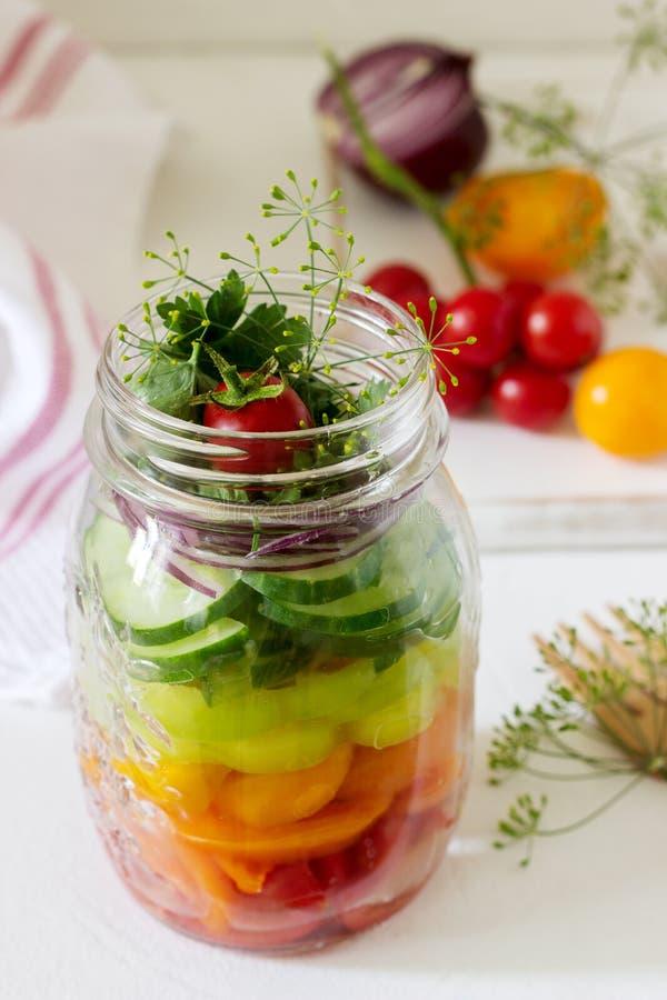 Sałatka warzywa z ziele w szklanym słoju i świezi warzywa na stole zdjęcie royalty free