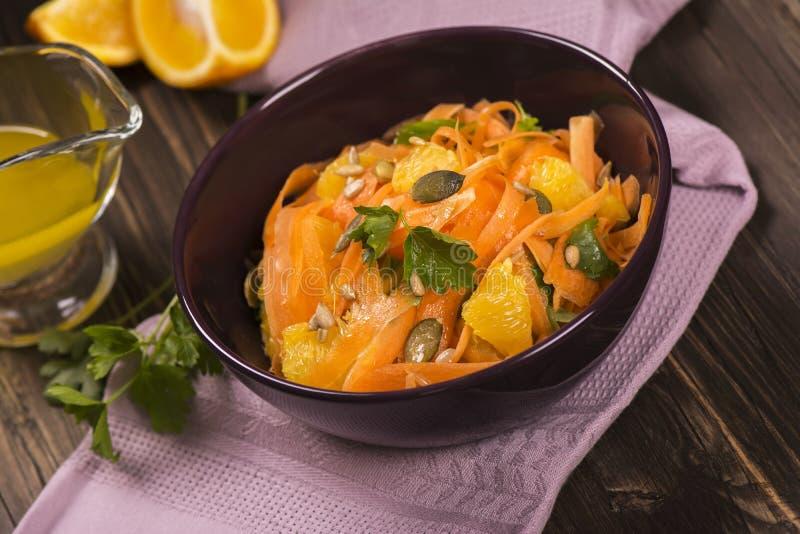 Sałatka z świeżą marchewką, pomarańczowymi plasterkami, banią i słonecznikowymi ziarnami, obrazy stock