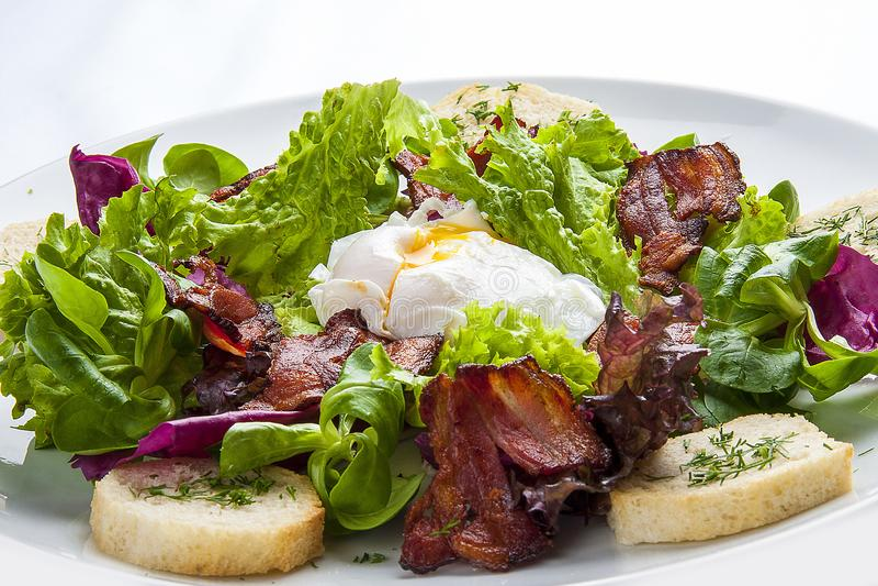 Sałatka z bekonem i kłusującym jajkiem na białym talerzu zdjęcia stock