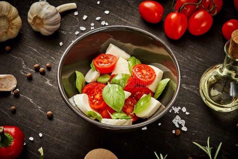 Sałatka z czereśniowymi pomidorami mozzarella i basil w pucharze na czarnym stole zdjęcia stock