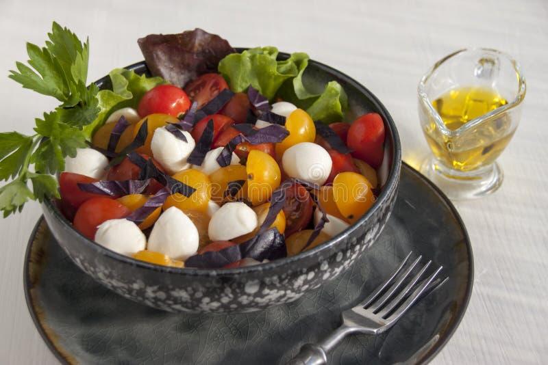 Sałatka z mozzarellą, czereśniowymi pomidorami, basilem i sałatą, obrazy stock