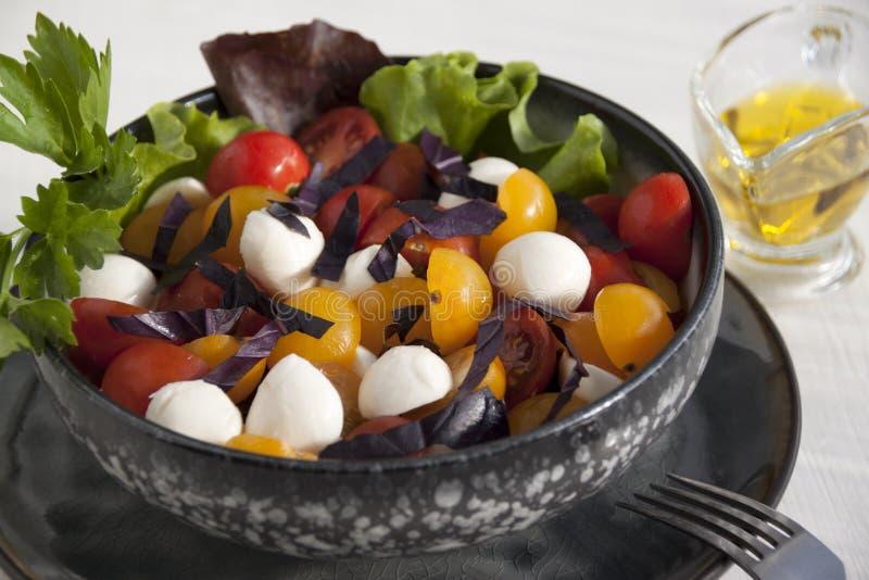 Sałatka z mozzarellą, czereśniowymi pomidorami, basilem i sałatą, zdjęcie stock