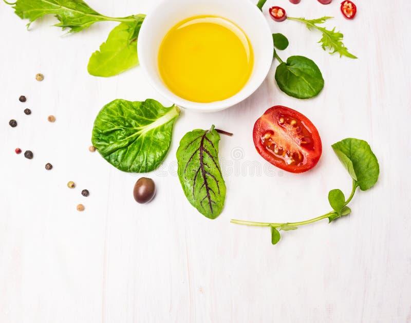 Sałatka z opatrunkiem, oliwkami i pomidorami na biały drewnianym, fotografia stock