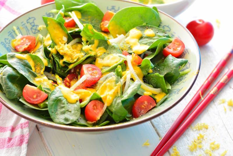 Sałatka z szpinakiem, cebulami, pomidorami i żółtym turmeric opatrunkiem, fotografia stock