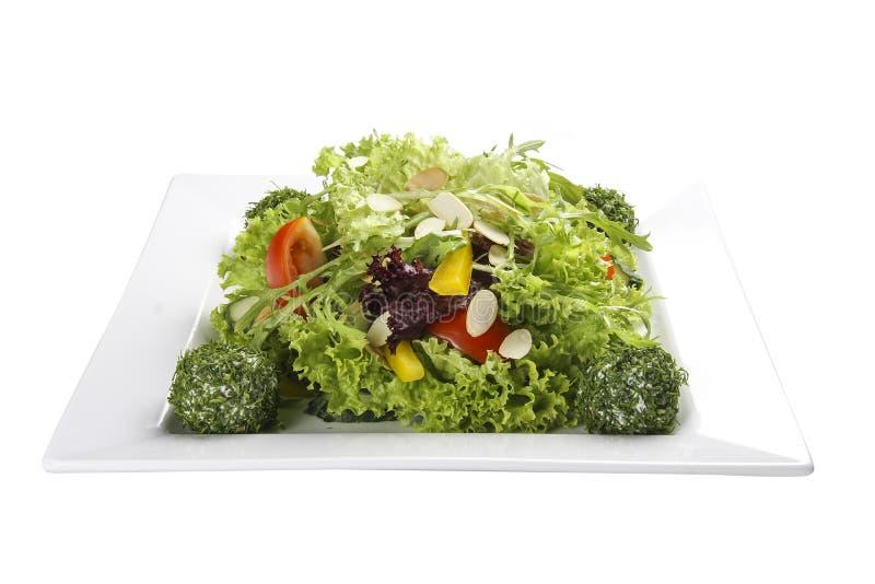 Sałatka z warzywami i serowymi piłkami na białym talerzu zdjęcia stock