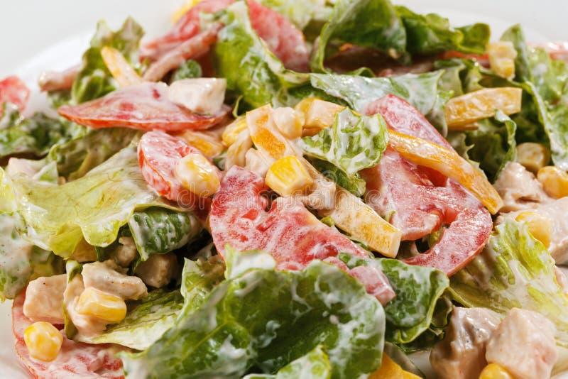 Sałatka z warzywami, kukurudzą, zieleniami i pomidorem w talerzu na odosobnionym białym tła zbliżeniu, zdjęcia royalty free