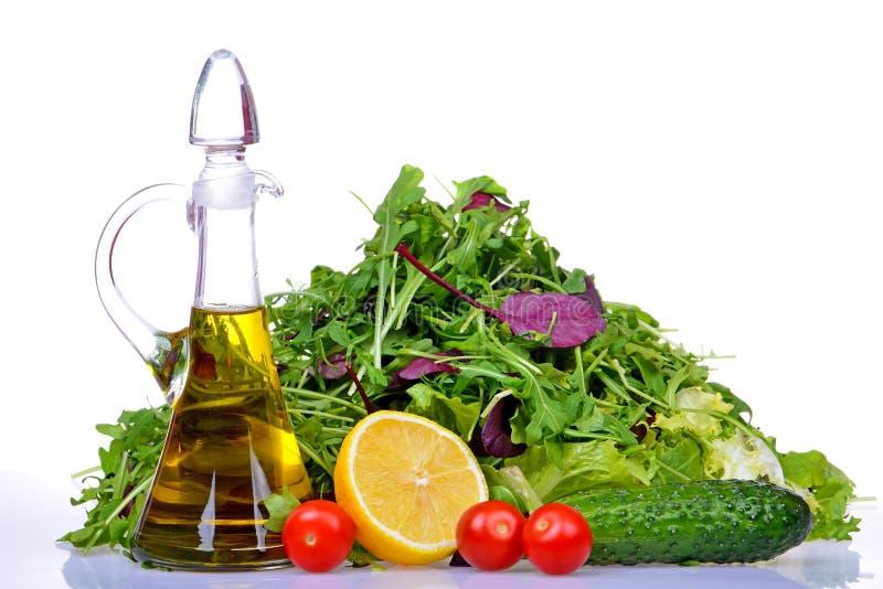 Sałatkowa mieszanka z rucola, frisee, radicchio, sałatą i butelką oliwa z oliwek, cytryna zdjęcia royalty free