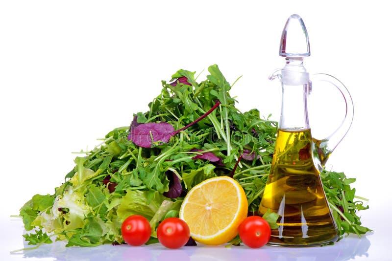 Sałatkowa mieszanka z rucola, frisee, radicchio, sałatą i butelką oliwa z oliwek, cytryna zdjęcie royalty free