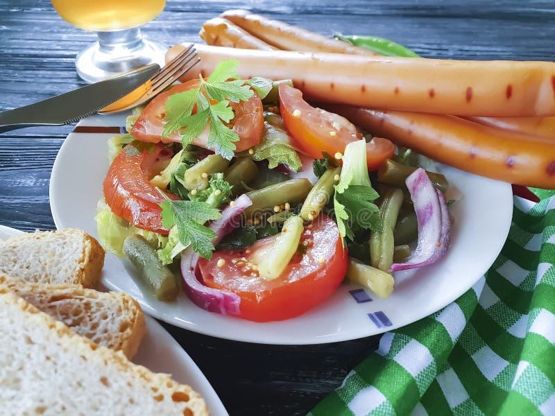 Sałatkowe fasolki szparagowe, pomidor, smażący wołowiien cebul kiełbas przekąski zakąski tradycyjny piwo na drewnianym tło grilla fotografia stock
