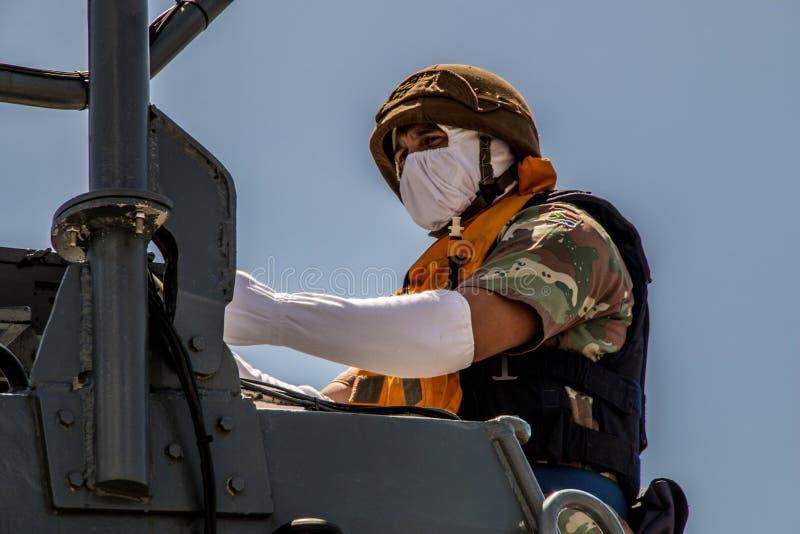 SA το μέλος ναυτικού επανδρώνει τα πυροβόλα όπλα σε μια βάρκα στοκ εικόνες