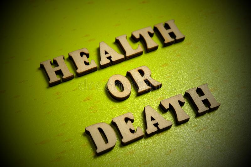 sa?de ou morte Conceito a inscrição de letras de madeira em um fundo verde vignetting imagens de stock