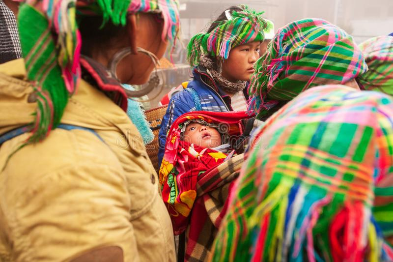 Tribe Hmong baby infant open beautiful eyes and looking around hmong family. Hmong women vendor in traditional clothing selling royalty free stock images