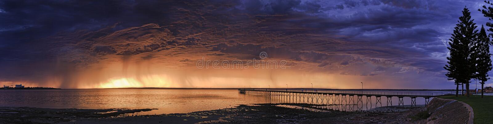 SA Sea Ceduna Bay Jetty Right. Wide sunset panorama of sun touching horizon over Great Australian bight during sea storm under heavy clouds as seen from Ceduna stock photography