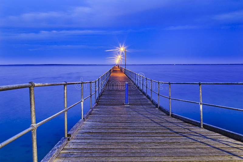 SA Sea Ceduna Jetty Surface Blue. Long wooden historic jetty in town of Ceduna, South Australia, at sunrise. Outstanding jetty construct goes towards open water royalty free stock photography