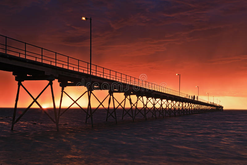 SA Sea Ceduna Red Jetty 2 hell. Red hellish sunset over sea horizon behind historic timber jetty of Ceduna town on Great Australian Bight. STormy weather makes stock photos