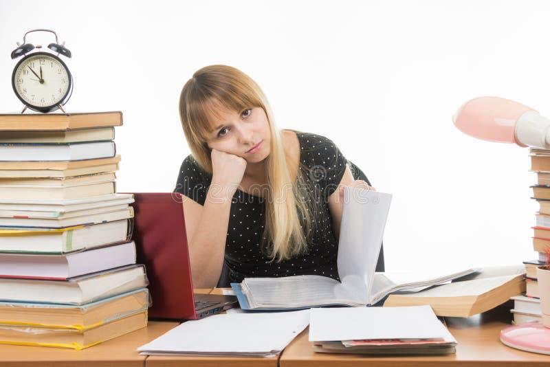 Saaie studenten het document doorbladert bij lijst onder boeken en stapels blikken in het beeld royalty-vrije stock afbeelding