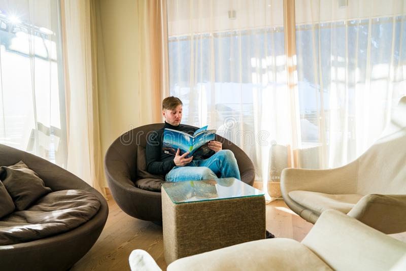 Young man sitting in a chair reading a book in a comfortable library room near huge windows. stock images