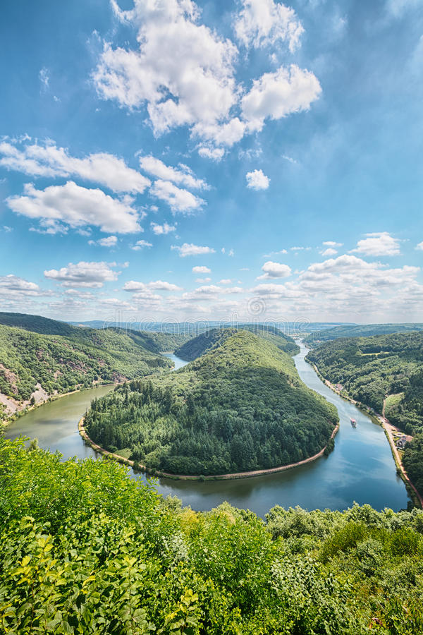 Saar River Bend - Saarschleife. The river Saar bend near Mettlach in Germany, also known as Saarschleife. Vantage point view from Cloef with blue sky and a few royalty free stock photo