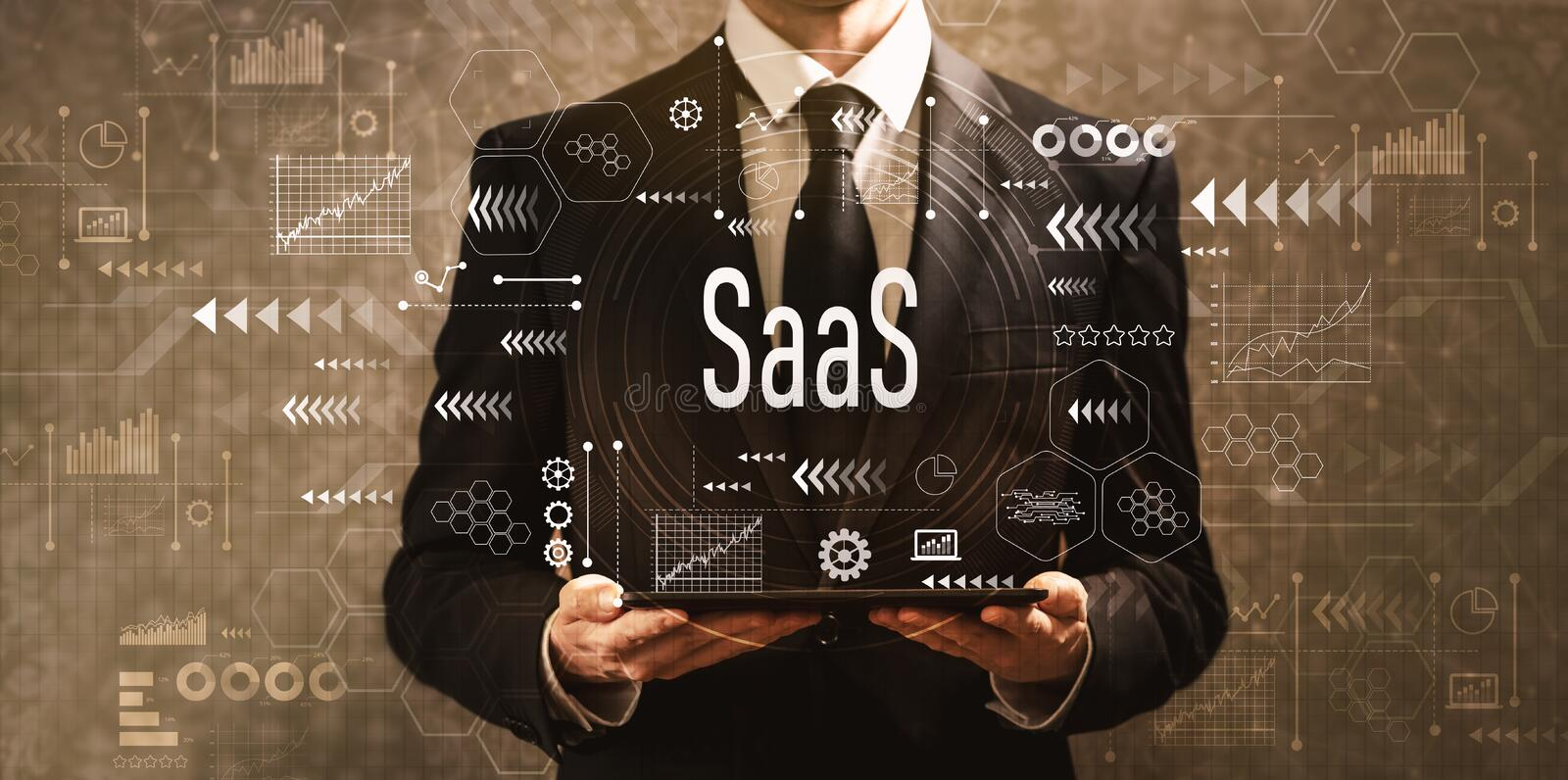 SaaS with businessman holding a tablet computer. On a dark vintage background stock photography